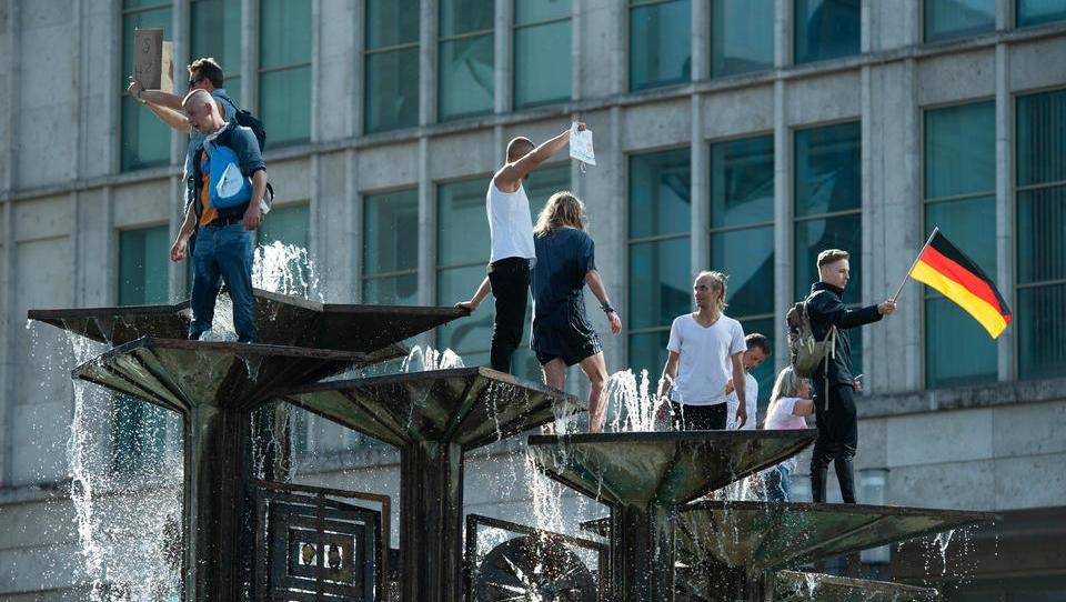"""I disordini a Berlino. Giovani manifestanti sulla """"Fontana delll'amicizia fra i popoli"""""""